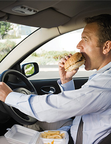 Man eating unhealthy food while driving